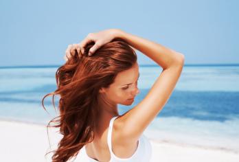 donna in spiaggia con mani tra i capelli